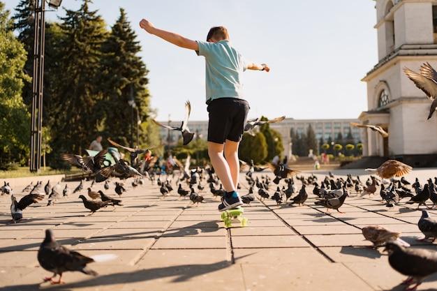 Chłopiec jedzie na pokładzie grosza w parku w ciepły letni czas z gołębiami i niebem