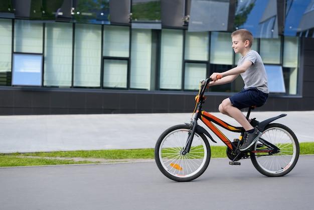 Chłopiec jedzie na rowerze sam na ulicy