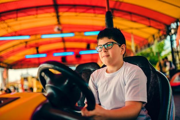 Chłopiec jedzie zderzaka samochód w parku rozrywki