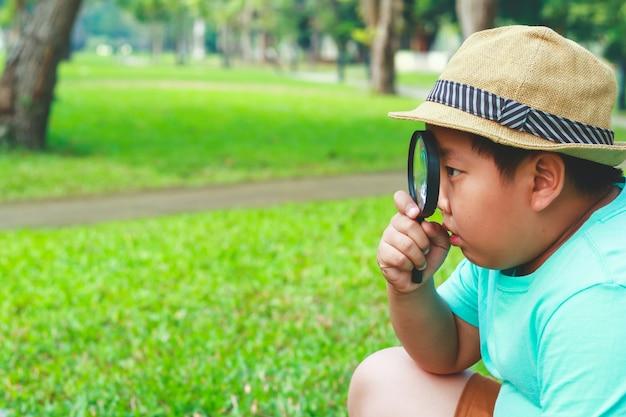 Chłopiec jest ciekawy. użyj lupy, aby spojrzeć na drzewo. w godzinach szkolnych