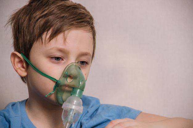 Chłopiec jest leczony nebulizatorem, aby pozbyć się kaszlu, leczyć zapalenie płuc, koronawirusa, zapalenie oskrzeli