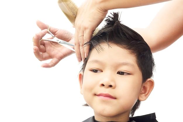 Chłopiec jest pocięte włosy przez fryzjer samodzielnie na białym tle