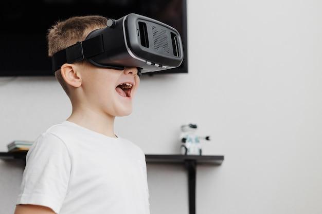 Chłopiec jest szczęśliwy, ponieważ używa zestawu słuchawkowego do rzeczywistości wirtualnej