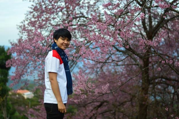 Chłopiec jest szczęśliwy widząc wiśniowe kwiaty.