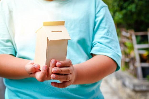 Chłopiec jest ubranym błękitną koszula trzyma drewnianego dom. skarbonka do przechowywania w przyszłości