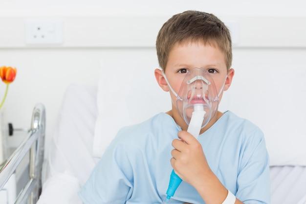 Chłopiec jest ubranym maskę tlenową w łóżku szpitalnym