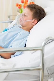 Chłopiec jest ubranym maskę tlenową w łóżku