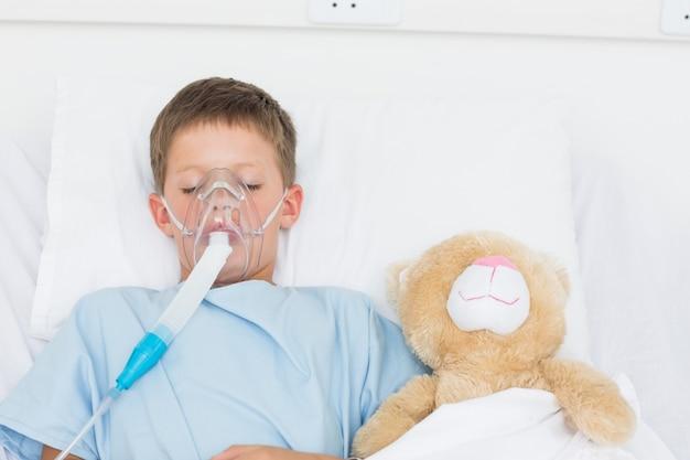 Chłopiec jest ubranym maski tlenowej dosypianie obok faszerującej zabawki