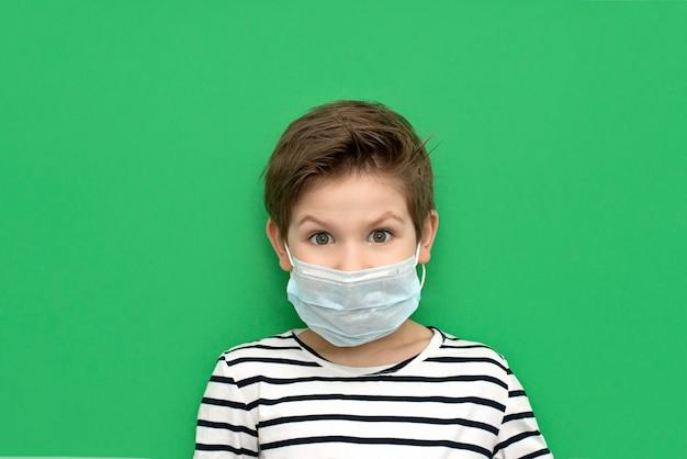 Chłopiec jest ubranym medyczną maskę odizolowywającą podczas koronawirusa.