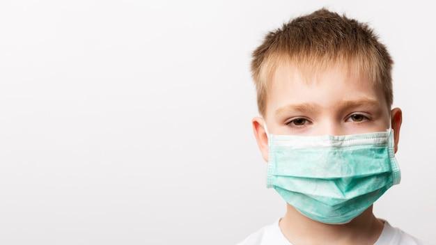 Chłopiec jest ubranym medyczną maskę
