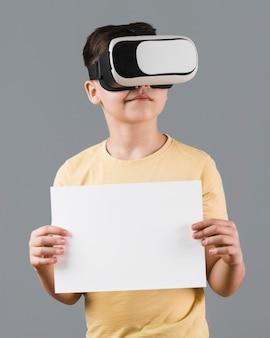 Chłopiec jest ubranym słuchawki wirtualnej rzeczywistości i trzyma pustego papier