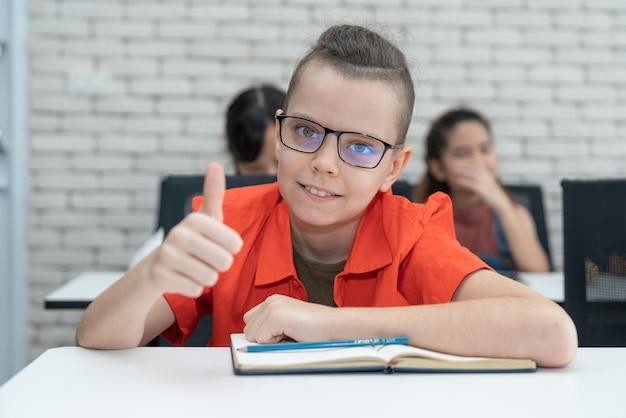 Chłopiec jest ubranym szkło uśmiech pokazuje aprobata gest w sala lekcyjnej