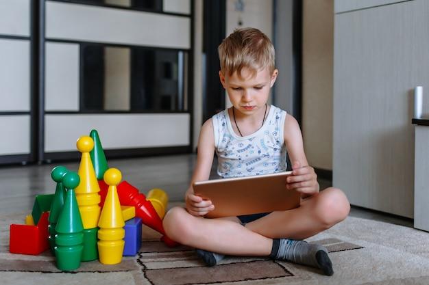 Chłopiec jest w pokoju gier obok zabawek, ale nie gra, ale patrzy na tablet
