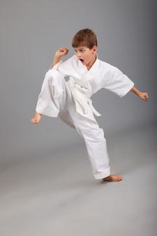 Chłopiec karate w białym kimonie