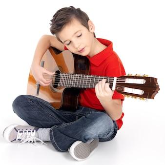 Chłopiec kaukaski gra na gitarze akustycznej - na białym tle