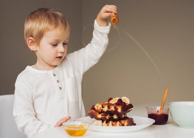 Chłopiec kładzenia miód na gofrze