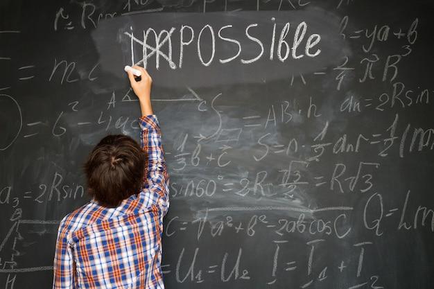 Chłopiec kładzie krzyż na tablicy niemożliwe