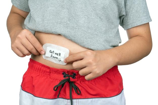 Chłopiec kładzie plaster na brzuchu z napisem