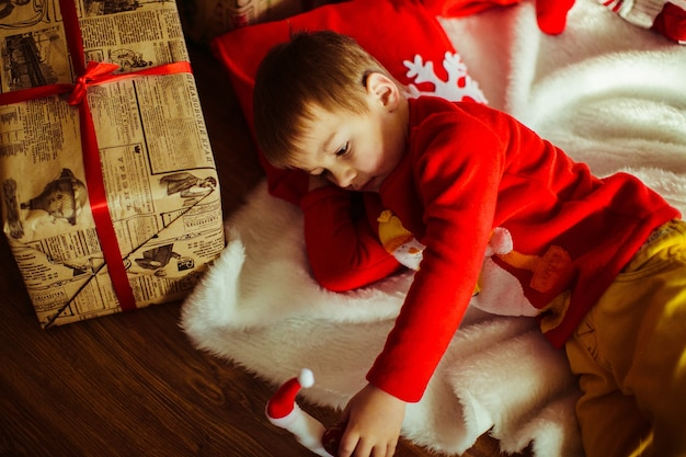 Chłopiec kłama na białym dywanie przed choinką