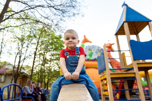 Chłopiec, kołysząc się na karuzeli na placu zabaw na ulicy