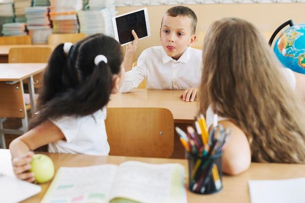 Chłopiec komunikuje się z dziewczynkami w klasie