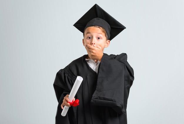 Chłopiec kończy studia nakrywkowego usta z rękami na popielatym tle