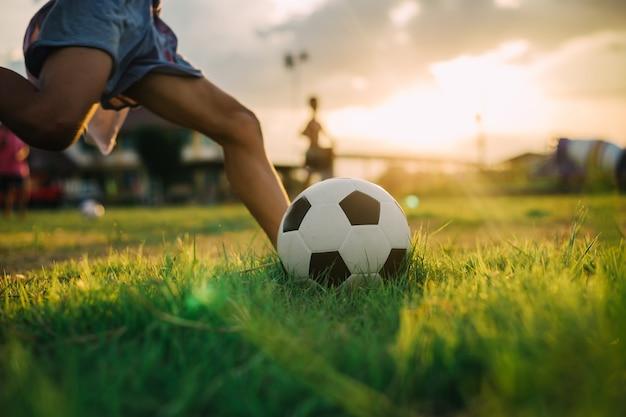 Chłopiec kopie piłkę bosą stopą podczas gry w piłkę nożną ulicy na polu zielonej trawie