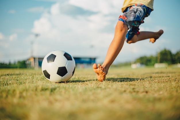 Chłopiec kopie piłkę bosą stopą podczas gry w piłkę nożną