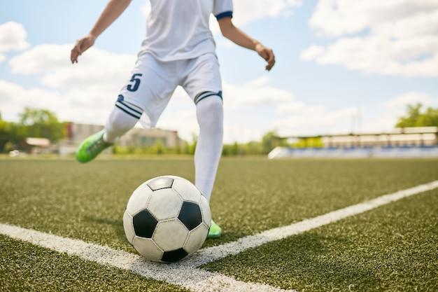 Chłopiec kopie piłkę na boisku piłkarskim