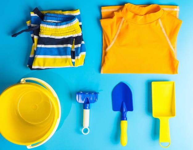 Chłopiec kostium kąpielowy i akcesoria plażowe płaskie leżał na temat wakacji letnich