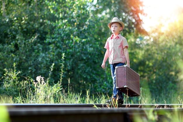 Chłopiec kowboj z walizką czeka na pociąg i kolejową koncepcję zachodniej podróży