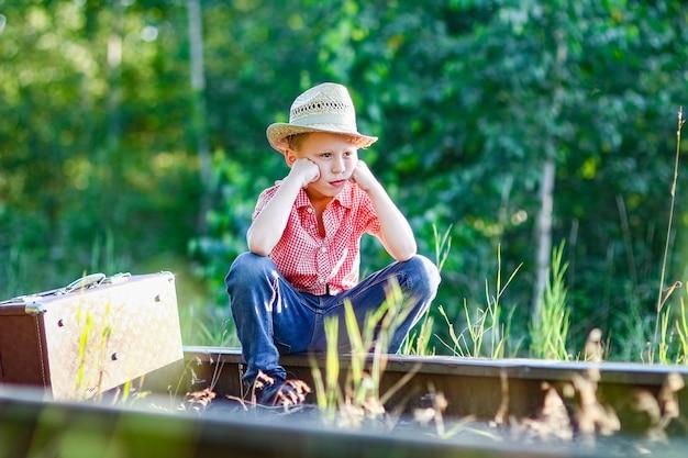 Chłopiec kowboj z walizką i kolejową zachodnią koncepcją podróży