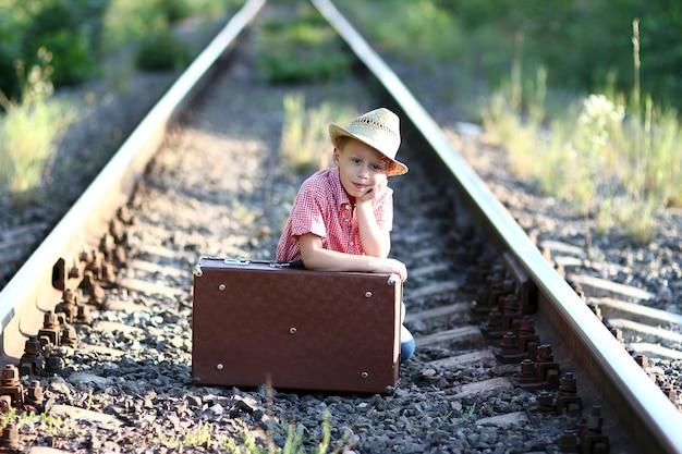Chłopiec kowboj z walizką i zachodnią koncepcją podróży kolejowej