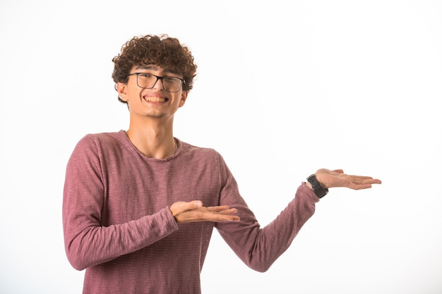 Chłopiec kręcone włosy w okularach optique, pokazując coś i śmiejąc się.