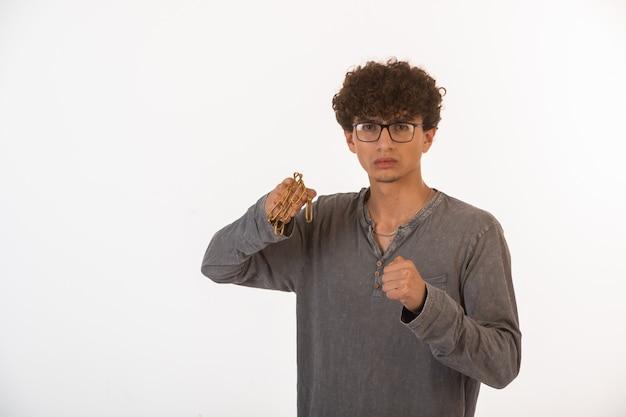 Chłopiec kręcone włosy w okularach optique trzyma metalowy łańcuch i jest gotowy do walki.