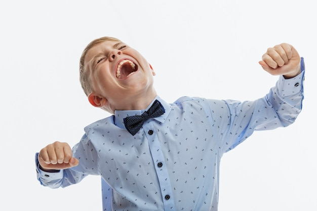 Chłopiec krzyczy emocjonalnie. dziecko 9-10 lat w niebieskiej koszuli. trudności w komunikowaniu się i uczeniu się. białe tło.