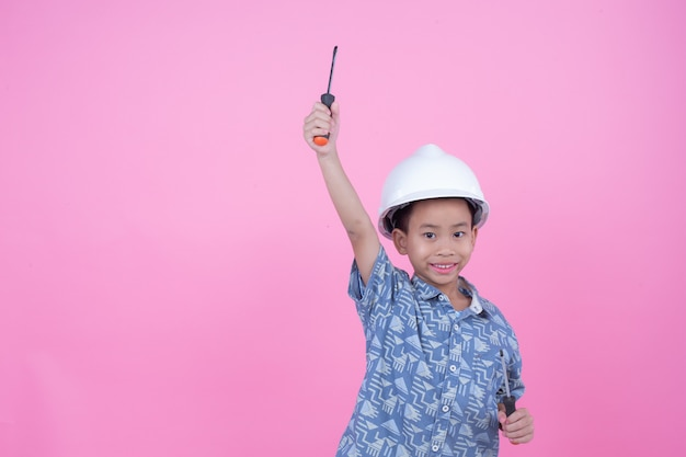 Chłopiec, który wykonał gest z rąk w hełmie na różowym tle.