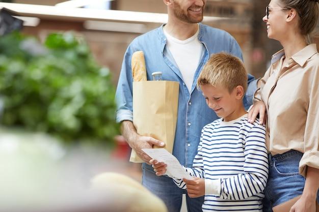 Chłopiec kupuje artykuły spożywcze z rodziną