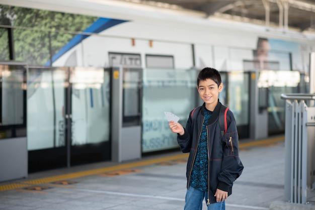 Chłopiec kupuje elektrycznego bilet i chodzi w jawnym niebo dworcu z rodziną