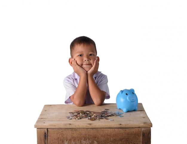 Chłopiec ładny kraj azjatyckich myśleć z piggy bank i monety na białym tle
