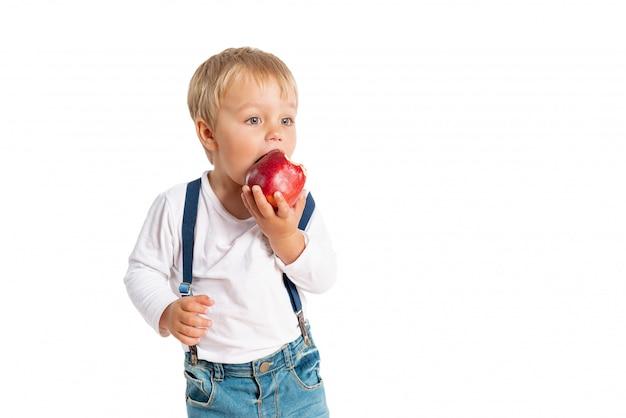 Chłopiec łasowania jabłko i ono uśmiecha się w studiu odizolowywającym