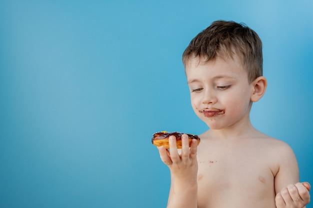 Chłopiec łasowania pączka czekolada na błękitnym tle. śliczny szczęśliwy chłopiec posmarowany czekoladą wokół ust. koncepcja dziecka, smaczne jedzenie dla dzieci