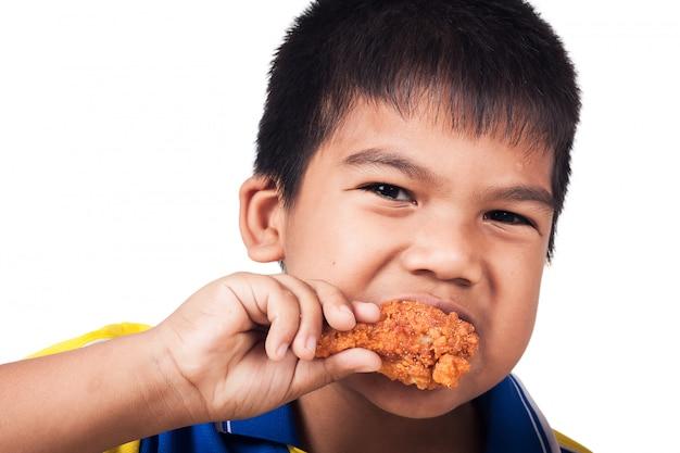 Chłopiec łasowania pieczony kurczak odizolowywa tło