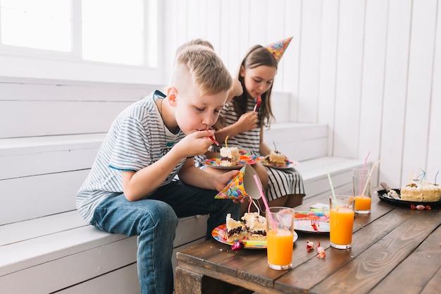 Chłopiec łasowania tort na przyjęciu urodzinowym z przyjaciółmi