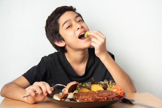 Chłopiec łasowania wieprzowiny ziobro grill z szczęśliwą twarzą