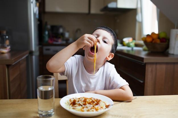 Chłopiec łasowanie z jego ręka makaronu naczyniem