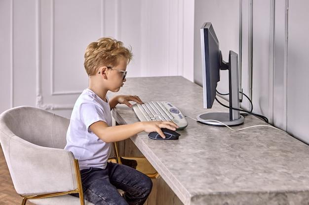 Chłopiec lat w okularach siedzi za komputerem do nauki