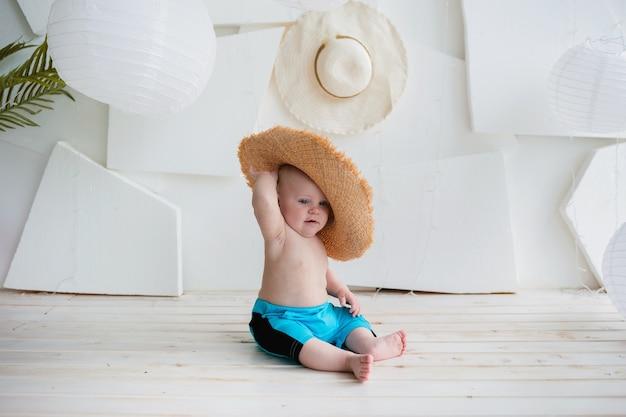 Chłopiec latem dziecko w niebieskie szorty i słomkowy kapelusz siedzi na białej powierzchni z miejscem na tekst