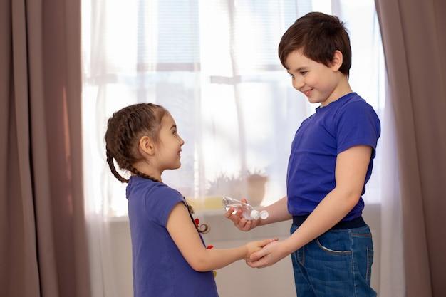 Chłopiec leczy antybakteryjny żel do rąk swojej młodszej siostry