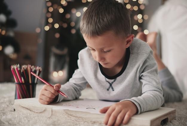 Chłopiec leżący z przodu i rysunek